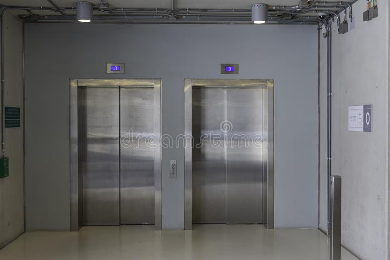Closed elevators with buttons in corridor with concrete walls. stock photo