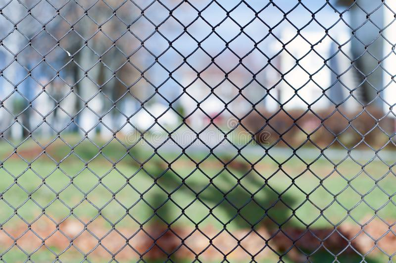 Closeup of black metal netting wire mesh fence against green field meadow. Texture pattern surface background of chain link wire-. Mesh rabitz stock images