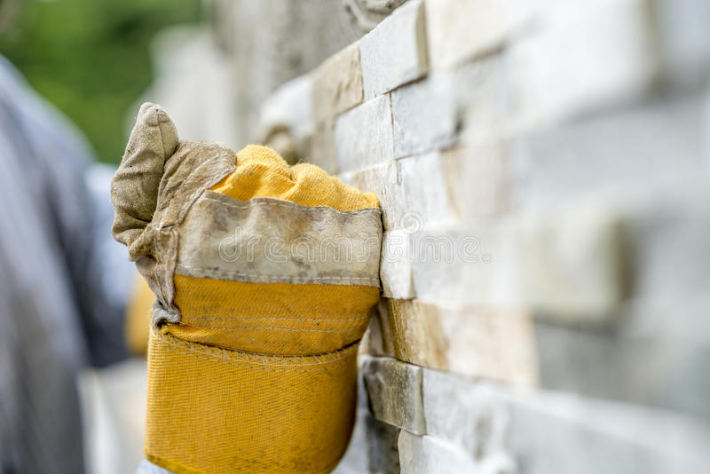 Closeup of manual worker in protection gloves tiling a wall wit stock image