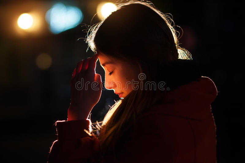 Closeup portrait of a young woman praying royalty free stock photos
