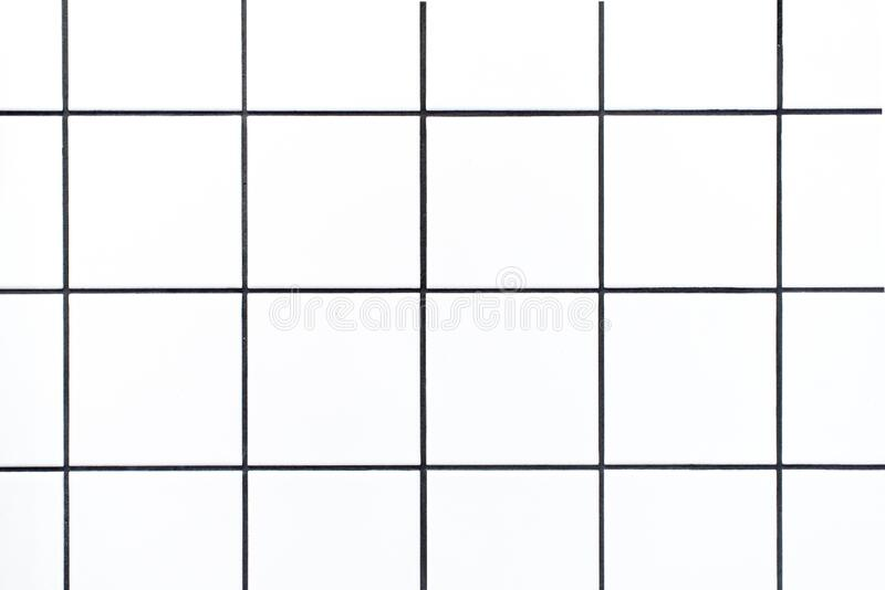 Closeup shot of small white square tiles with black grout lines, close up of tiled bathroom wall as background or backdrop. Closeup shot of small white square royalty free stock images