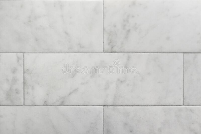 Closeup of subway tile carrara marble wall background. Closeup of subway tile carrara marble wall making a seamless background stock image