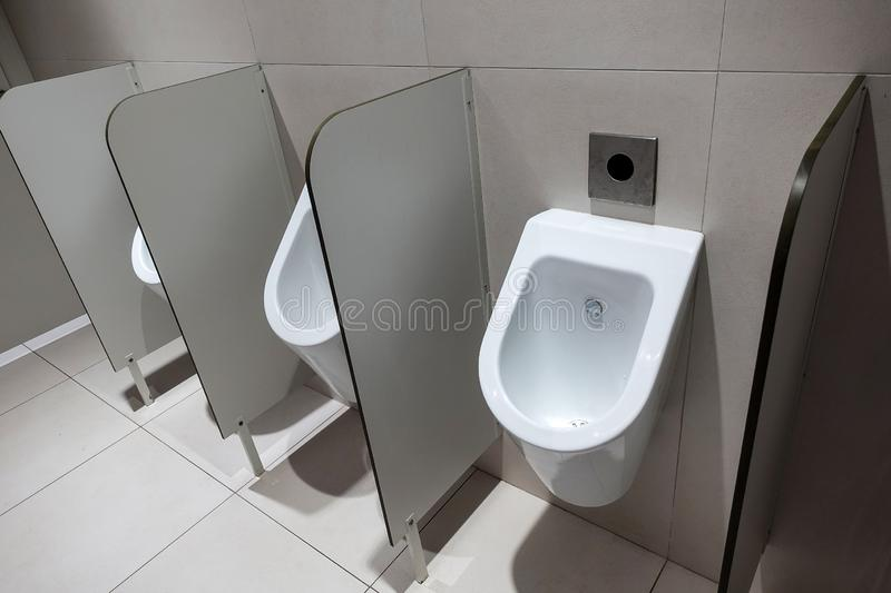 Closeup of three white urinals in men`s bathroom design of white ceramic urinals for men in toilet room, Loft wall.  royalty free stock photos