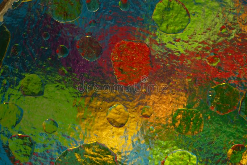 Colored objects through corrugated glass when mixing water and oil. stock image