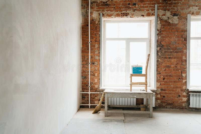 Concept repair. plaster of windows and walls of red brick. Large windows in the room, a construction goat, a chair and a bucket wi stock image