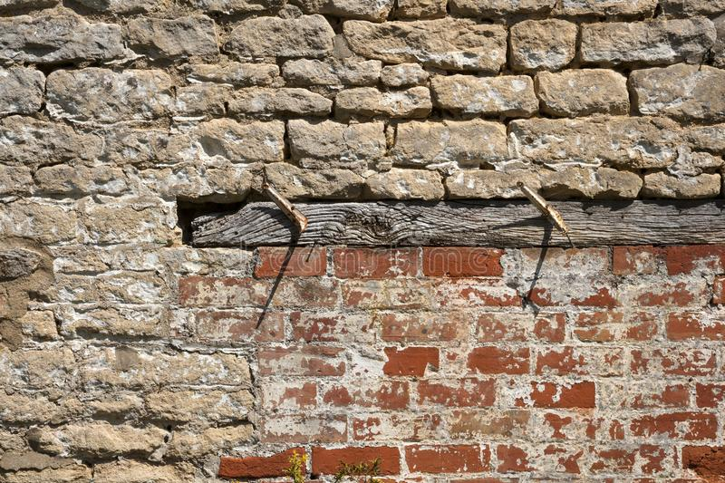 Construction background - an old brick wall needs repairs. An old weathered brick and stone wall needs repairs. Construction full frame texture background stock photography