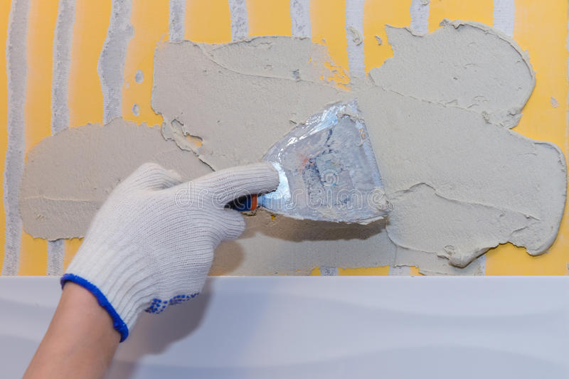 Construction work laying tile on the wall stock image