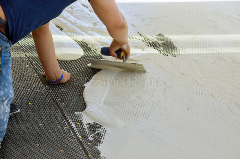 A construction worker troweling mortar onto concrete floor in preparation for laying floor tile. A construction worker troweling mortar onto a concrete floor in stock image