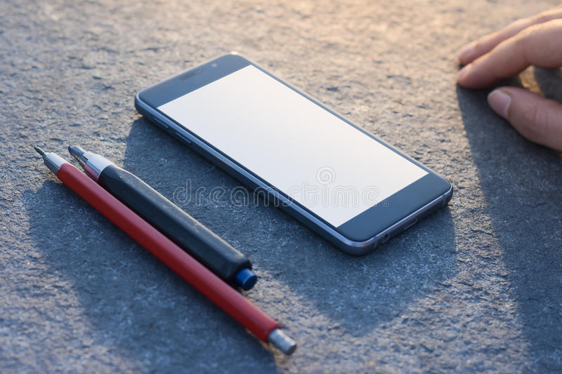 Contemporary modern smartphone on stone finishing background. Pencils and hand. Visual effects. Blank display replaceable with needed design.Vertical mockup stock image