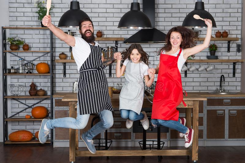 Cooking with child might be fun. Having fun in kitchen. Family mom dad and little daughter wear aprons jump in kitchen stock images