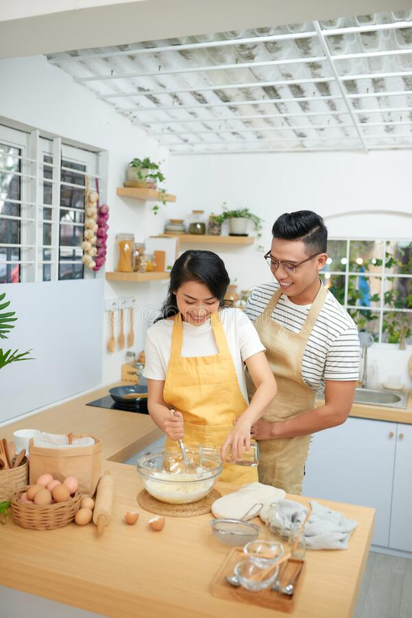 Couple man and woman wearing aprons having fun while making homemade pasta in kitchen at home stock photo