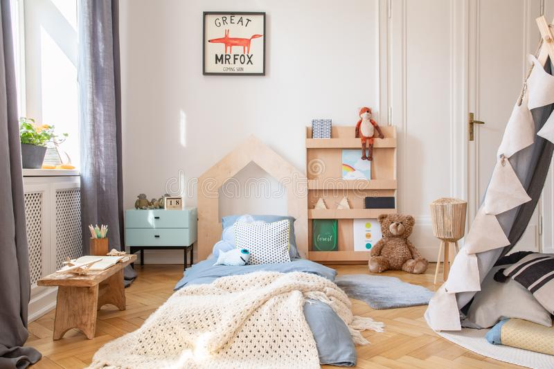 Cozy kids bedroom with blue bedding and warm blanket on the bed, real photo with mockup poster on the floor royalty free stock image