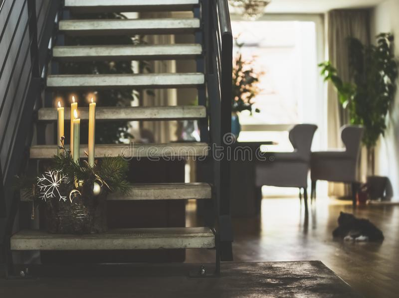 Cozy living room with stairs to second floor , winter decoration with burning candles on steps, window and cat. Winter holidays. Cozy living room with stairs to royalty free stock images