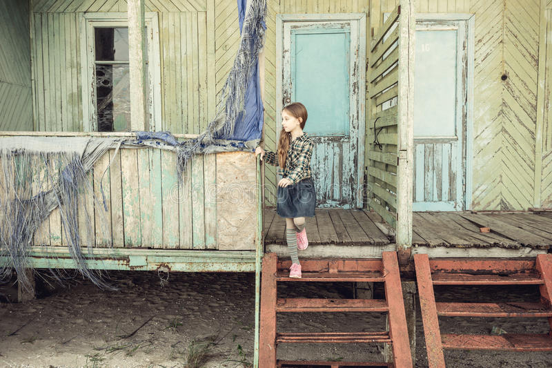 Cute little girl standing on stairs of abandoned wooden house. At a seaside royalty free stock photo