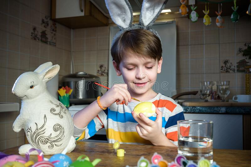 Cute preschool kid boy coloring eggs for Easter holiday in domestic kitchen, indoors. Child having fun with painting colors and. Preparing for traditional egg stock photos