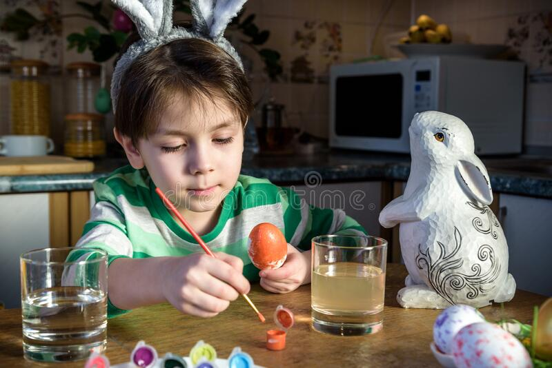 Cute preschool kid boy coloring eggs for Easter holiday in domestic kitchen, indoors. Child having fun with painting colors and. Preparing for traditional egg stock photography