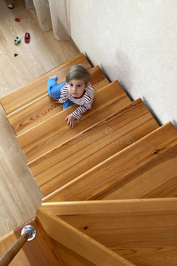 Cute young boy sitting on stairs on the second floor royalty free stock photo