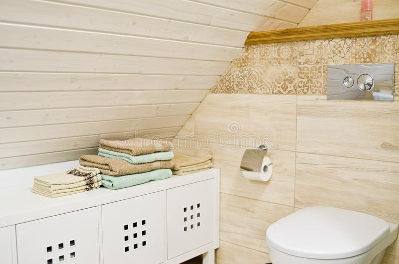 Loft bathroom with wooden ceiling detail. Detail of a cozy bathroom in a home, loft room with wooden or timber planks on the ceiling. Elegant interior design stock photography