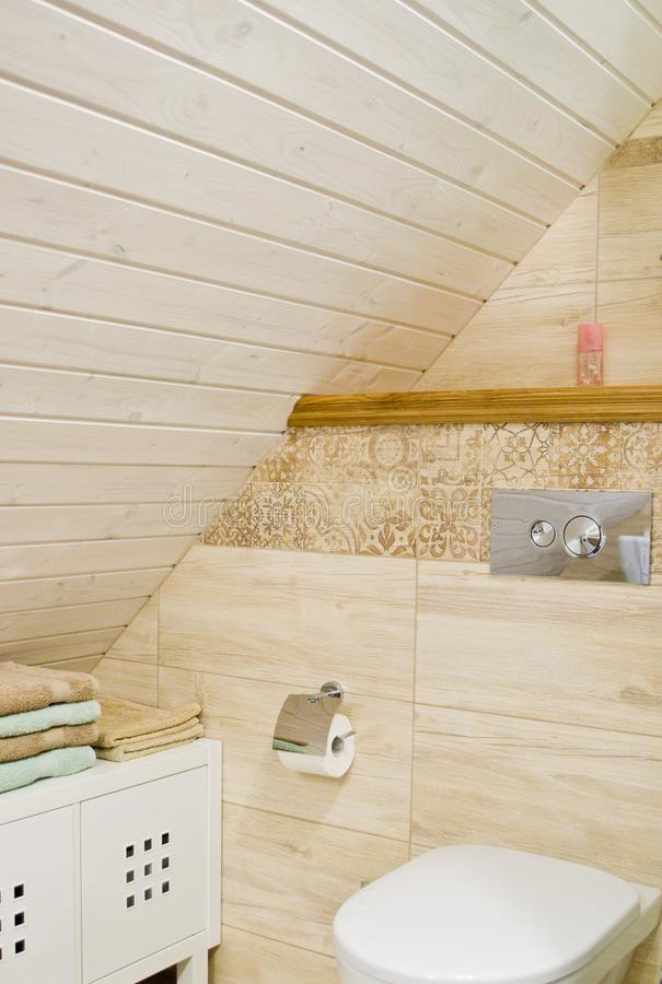 Loft bathroom with wooden ceiling detail. Detail of a cozy bathroom in a home, loft room with wooden or timber planks on the ceiling. Elegant interior design stock photos