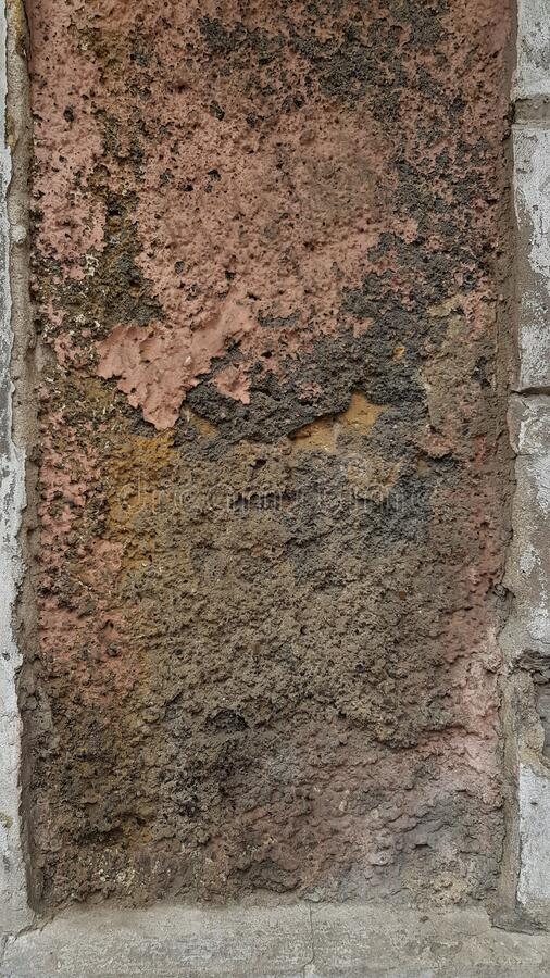 Grunge backdrop of old rough stone wall surface of ruined building. Dilapidated dirty wall texture closeup with damaged rough brown stucco surface. Grunge royalty free stock images
