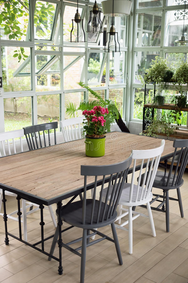 Dining room interior with table, chairs and plants against big w stock photography