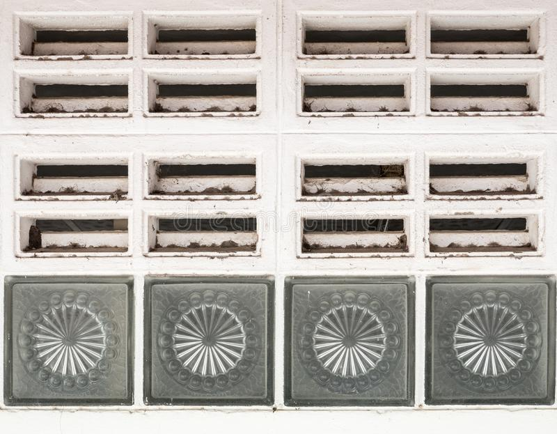 Dirty air ventilation grille. Dirty air ventilation grille with the glass box on the public toilet wall stock photography