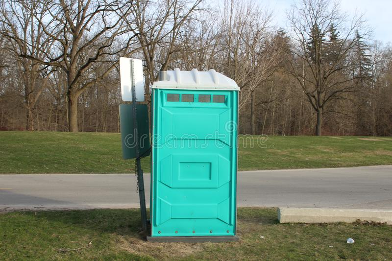 A Dirty, Blue Portable Toilet in a Park, nasty looking place to go to the bathroom. A Dirty, Blue Portable Toilet in a Park, with Scraps of Toilet paper royalty free stock photography