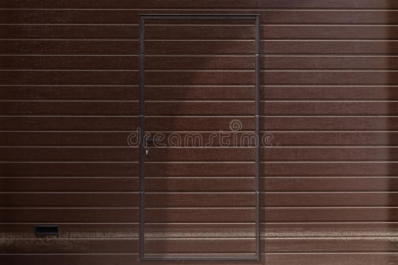 Doors in the color of the walls, walls patterned with wooden clapboard painted in brown, front view.  stock photos