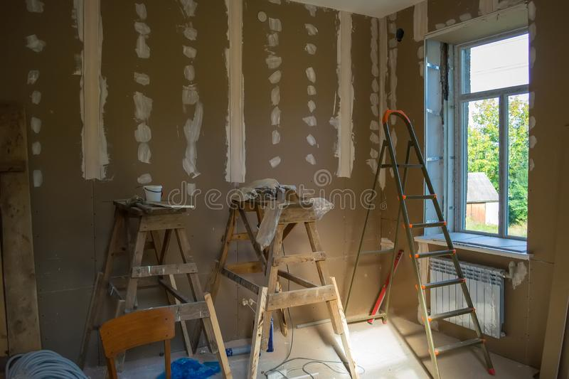 Drywall on the walls and working equipment during the repair of the room stock photography
