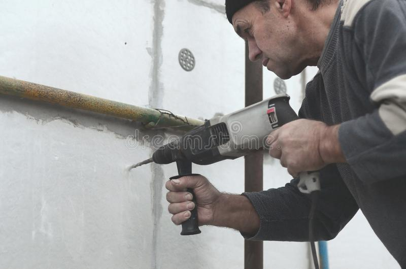 An elderly workman drills a hole in a styrofoam wall for the subsequent installation of a plastic reinforcing dowel. Creating royalty free stock photography