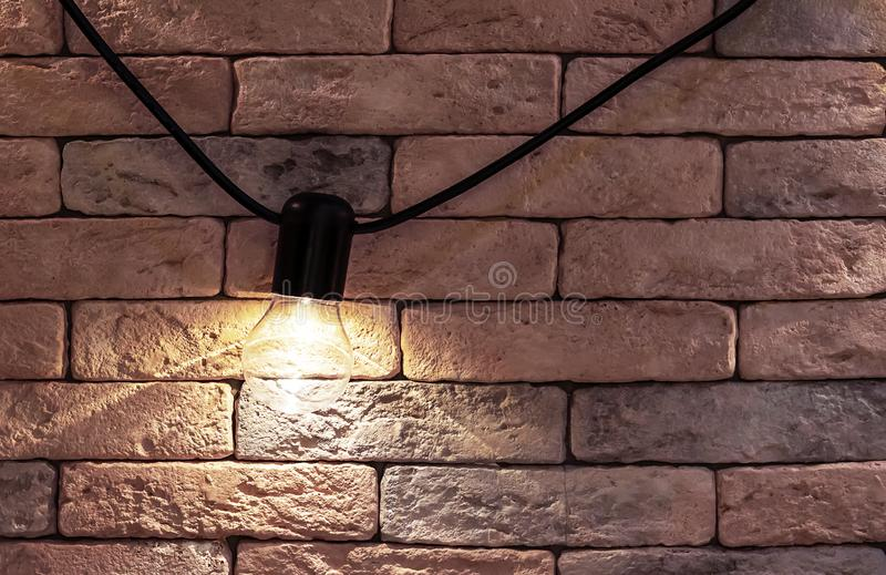 Electric lamp on a brick wall background. Loft style interior royalty free stock photo