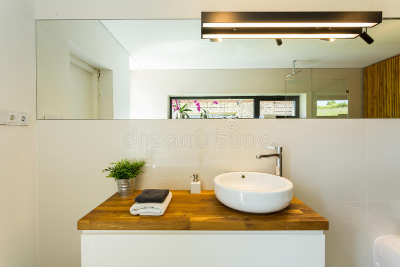 Elegant loft bathroom. Natural wood furniture in elegant loft bathroom interior stock photo