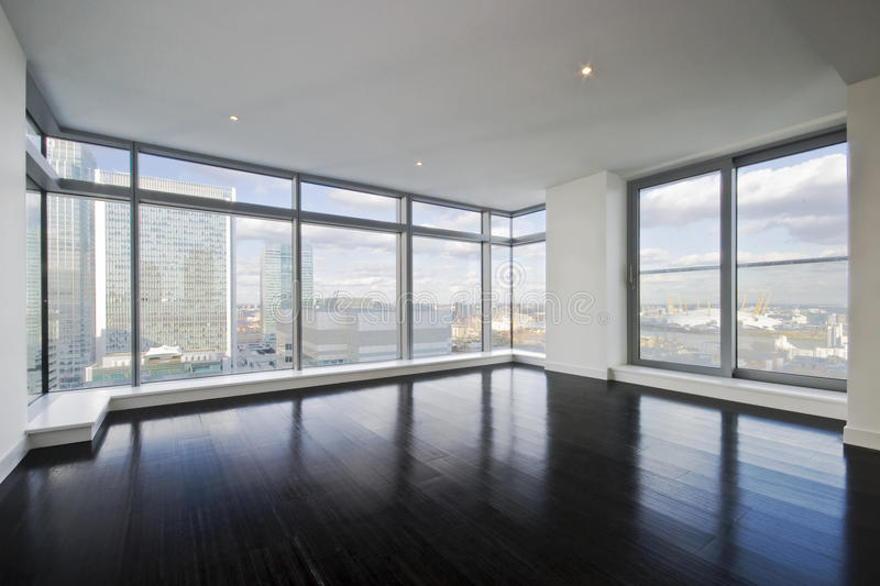 Empty apartment. With hard wood floor an floor to ceiling windows royalty free stock photos