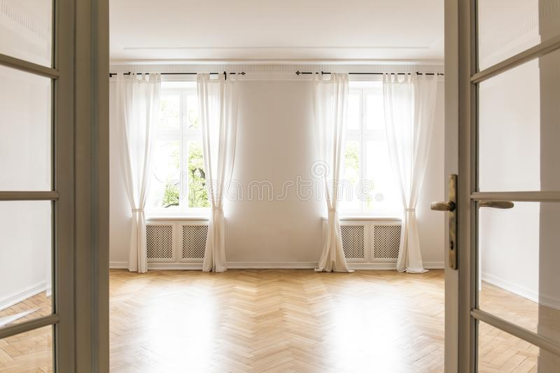 Empty bright living room interior with drapes at windows and woo stock images