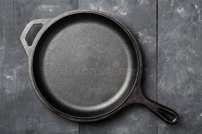 Empty, clean black cast iron pan or dutch oven top view from above on black table stock images