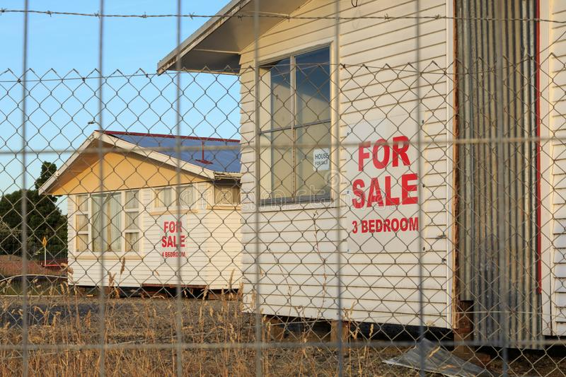 Empty houses for sale in a removal lot. Unoccupied houses with corrugated iron roofs and clapboard walls, removed from their foundations and placed in a lot for royalty free stock images