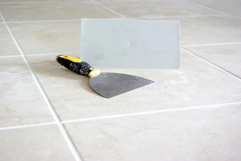 End of tiling. Tiling equipments on shiny new floor royalty free stock photo
