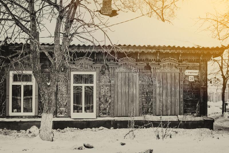 Facade of an old wooden house decorated with carvings in a traditional Russian style, monochrome, blurred image stock photos