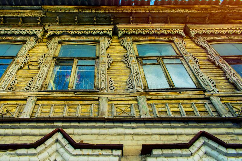 Facade of an old wooden house decorated with carvings in a traditional Russian style, perspective stock photo
