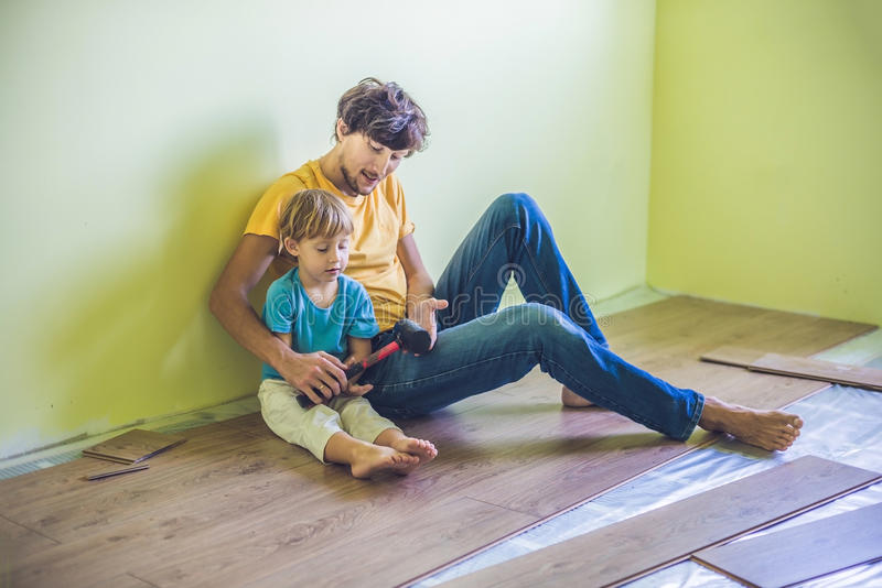 Father and son installing new wooden laminate flooring. infrared stock images
