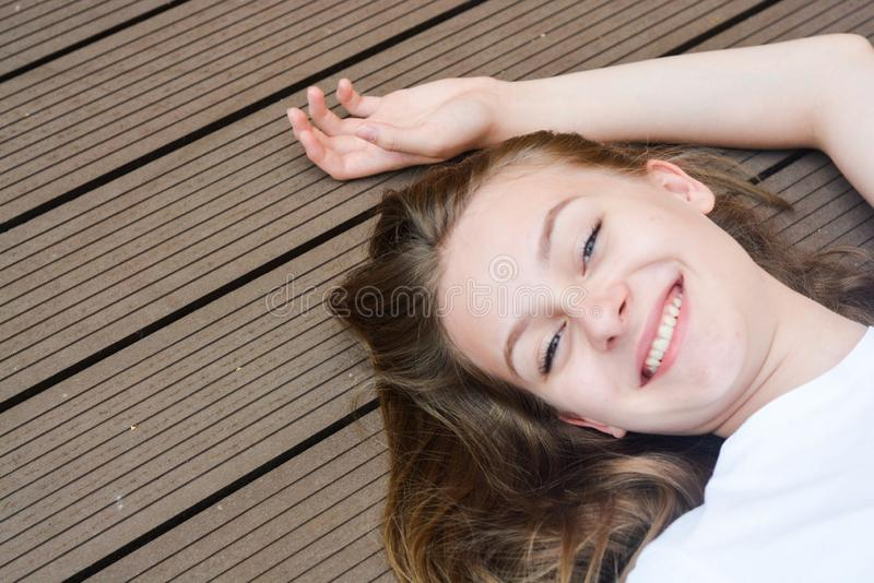 Female teenager smiling, layingon the floor. Summer, portrait of young girl with long, blonde hair stock image