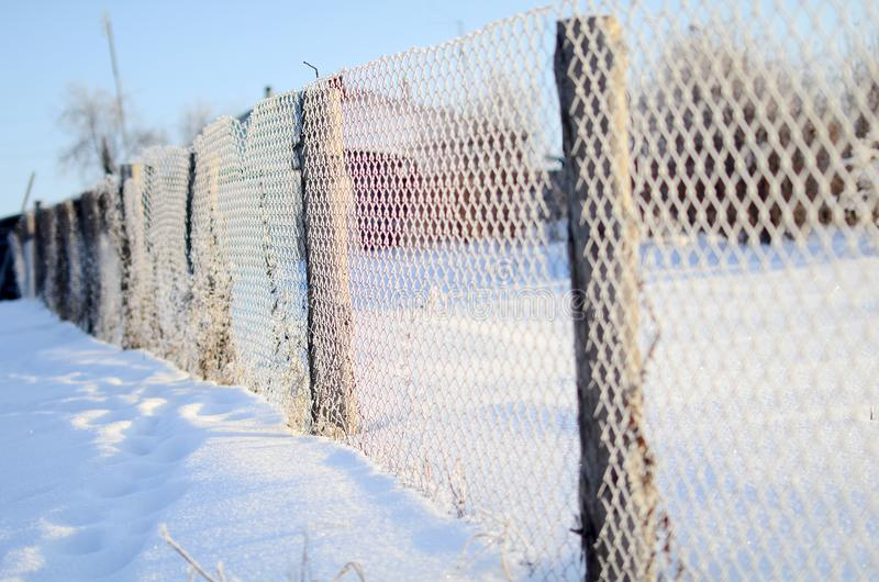 A fence of mesh netting covered with frost in a Sunny day. A fence of mesh netting in a Russian village on a clear Sunny winter day stock image
