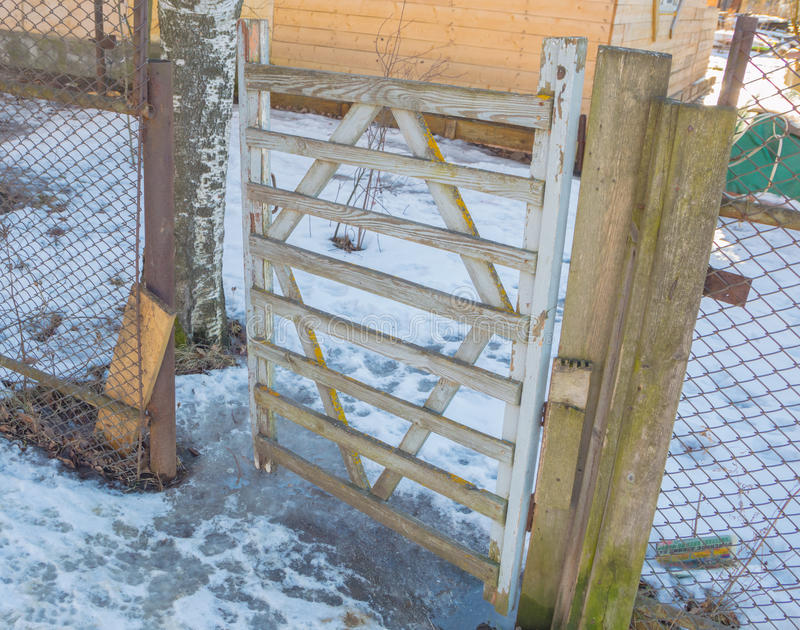Fence netting mesh with vintage wooden gate. In the winter an old wooden gate with mesh fence netting stock images