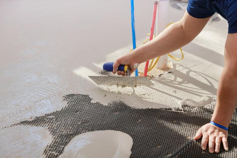 Floor preparation before pouring concrete in troweling adhesive onto a concrete floor. Preparation before pouring concrete in troweling adhesive onto floor a stock image