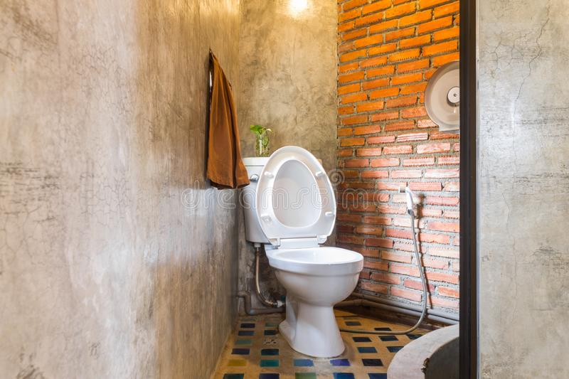 Flush Toilet in Country Loft Interior Design Room. Interior design room include towel and bathroom and toilet paper. Interior design room in part of toilet stock photo