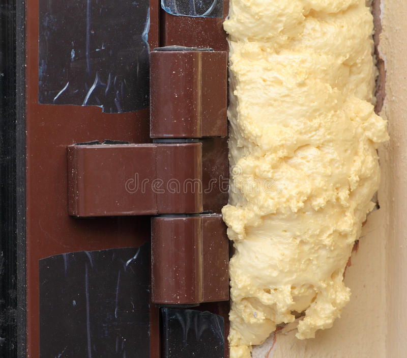 Foam insulation installation of entrance doors. Polyurethane insulation between door and wall royalty free stock images