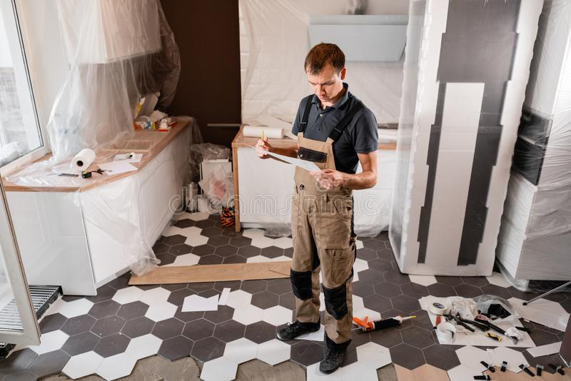Focused diligent worker inspecting room and planning repairs work. repair of the dining room in the house, kitchen royalty free stock photography