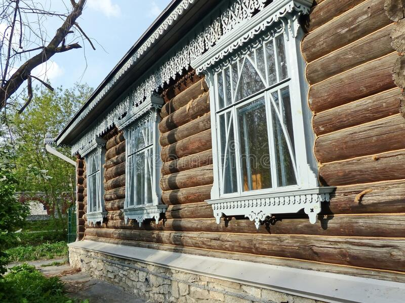 A fragment of the wooden facade hut. The window architraves. Folk art. Russian village. Old wooden houses. Monument of ancient Russian architecture. Golden stock photography