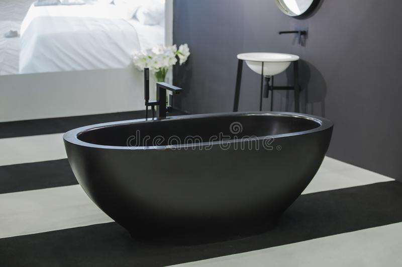 Freestanding black bathtub, stylish minimalist black and white loft style bathroom. Bath, washstand, mirror on the wall.  royalty free stock images