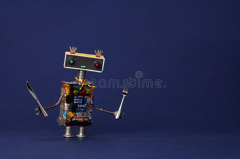 Friendly robot waiter with fork and knife. Food menu concept cute cooking kitchen chef toy character on dark blue stock photography
